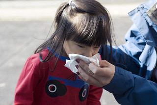 A girl sneezing into a handkerchief.